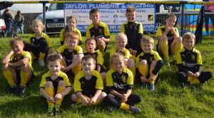 Lions Junior Rugby Team with Taylor Plumbing & Heating sign.
